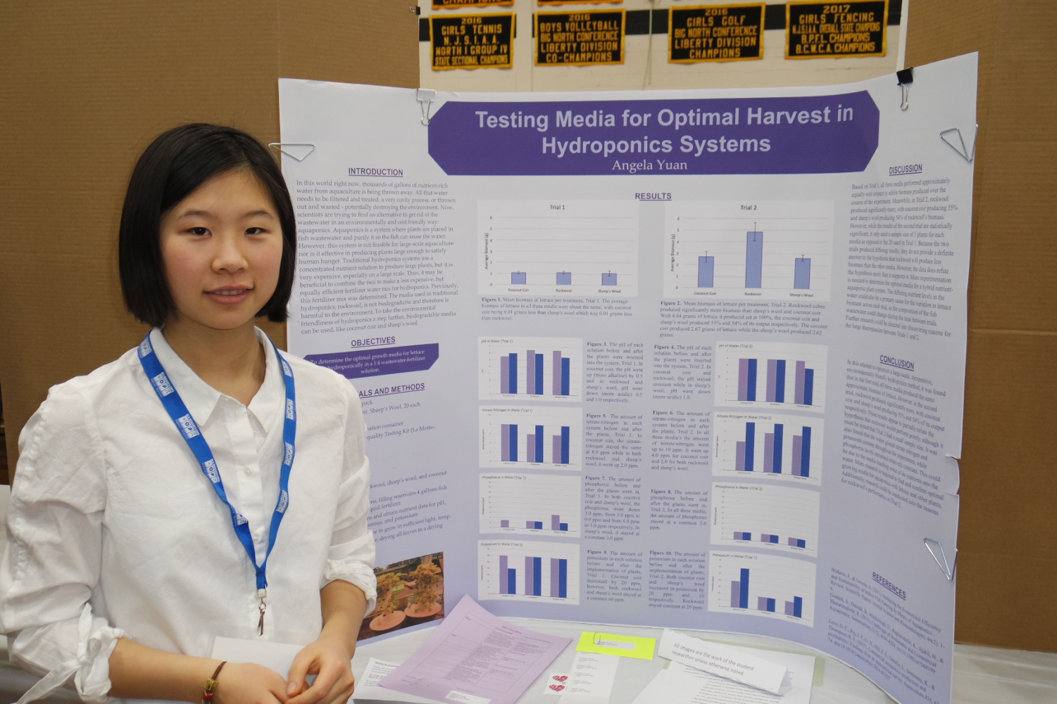 Angela Yuan, AAST junior, in front of her research poster on agriculture.