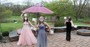 Image of three students from central Pennsylvania wearing masks and prom dresses